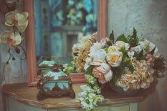 在桌上的人造花花束在卧室 免版税库存照片