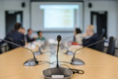 在桌上的会议话筒被弄脏到会者在会议室背景中 免版税库存图片