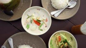 在桌上的传统亚洲烹调 地道泰国盘咖喱,汤姆kha汤和米顶视图  股票录像