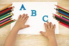 在桌上的儿童手 教育和字母表概念 在木背景的铅笔 库存照片