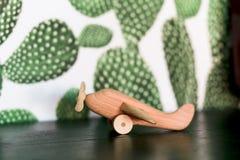 在桌上的减速火箭的木玩具飞机有仙人掌背景 库存图片