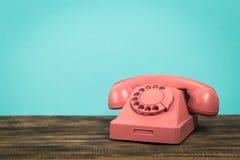 在桌上的减速火箭的桃红色电话在前面薄荷的绿色背景中 免版税库存照片