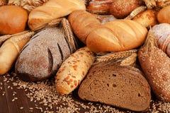在桌上的分类和麦子耳朵上添面包 免版税库存图片