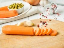 在桌上的切的红萝卜 烹调的大蒜豌豆葱胡椒菜 图库摄影