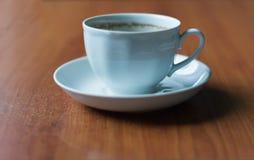 在桌上的加奶咖啡杯与泡沫踪影在边缘的 免版税库存照片