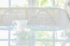 在桌上的加奶咖啡杯子有窗口基石背景 免版税库存图片