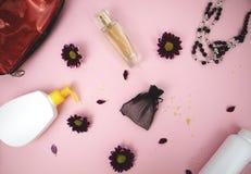 在桌上的化妆用品在妇女 化妆袋子、化妆用品和卫生学方面的产品 文本的桃红色背景 免版税库存图片