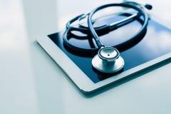 在桌上的医疗设备 蓝色听诊器和片剂 库存图片