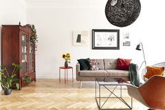 在桌上的向日葵在明亮的客厅内部的沙发旁边与海报和植物 实际照片 皇族释放例证