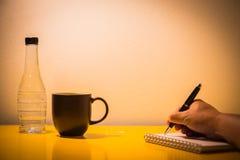 在桌上的咖啡杯塑料瓶和手文字与灯在 免版税库存图片