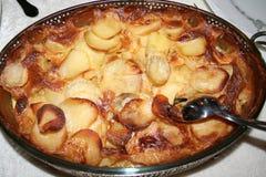 在桌上的土豆焦干酪对增殖比与肉,菜一起服务等等 免版税库存照片