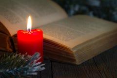 在桌上的圣经和圣诞节红色蜡烛在夜之前 免版税库存照片