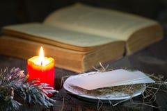在桌上的圣经和圣诞节红色蜡烛在夜之前 免版税库存图片
