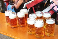 在桌上的大被填装的啤酒杯 库存照片