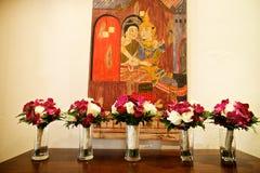 在桌上的婚礼花束与泰国绘画在背景中 库存照片