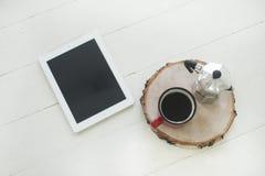 在桌上的工作区数字式片剂与在木桌上的黑屏与杯子 免版税库存图片