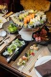 在桌上的开胃菜-寿司、沙拉和蜗牛 有选择性的focu 库存照片