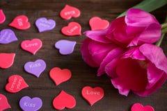 在桌上的心脏在花旁边 免版税库存图片