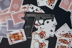 在桌上的手枪与卡片 免版税库存照片