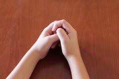 在桌上的手,两条胳膊,身体局部,木家具,儿童的手, 免版税库存照片