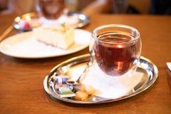 在桌上的接近的茶杯在与迷离光bokeh的咖啡馆 免版税库存图片