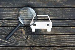 在桌上的放大镜和纸房子 免版税库存图片