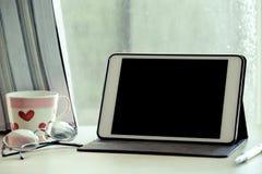 在桌上的数字式片剂在工作场所在雨天 免版税库存照片