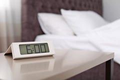 在桌上的数字式闹钟在卧室 免版税库存图片