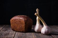 在桌上的新近地被烘烤的黑面包和大蒜谎言大面包  库存图片