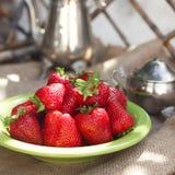 在桌上的新鲜的草莓在庭院里 免版税库存图片