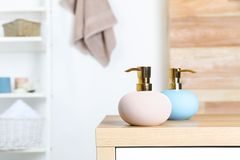 在桌上的时髦的肥皂分配器反对被弄脏的背景 图库摄影