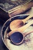 在桌上的木厨房器物 在一个减速火箭的样式的食谱书木匙子老平底锅在木桌上 免版税图库摄影
