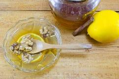 在桌上的核桃蜂蜜和柠檬 免版税库存照片