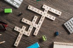 在桌上的概念性企业主题词与做纵横填字谜的比赛的元素 免版税图库摄影