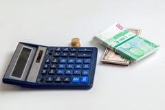在桌上的欧元和美元金钱在计算器旁边 库存图片