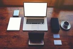 在桌上的演播室年轻设计师是一个时髦的膝上型计算机和辅助部件年轻成功的人 免版税库存照片