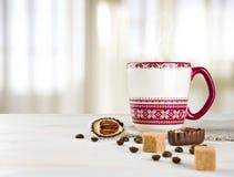 在桌上的热的咖啡杯在被弄脏的curtained窗口背景 免版税库存图片
