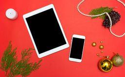 在桌上的片剂聪明的电话显示在大模型的红色屏幕上在圣诞节时间 圣诞树,装饰在背景中 库存照片