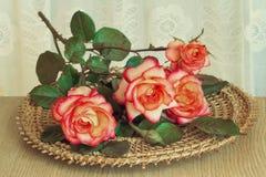 在桌上的玫瑰在一个柳条盛肉盘 免版税库存图片