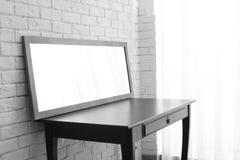 在桌上的现代镜子在墙壁附近 库存照片