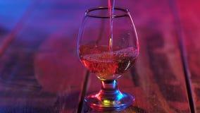 在桌上的玻璃身分在五颜六色的照明设备倒的科涅克白兰地 t 股票视频