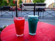 在桌上的甜冷的红色和蓝色鸡尾酒 免版税库存图片