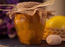 在桌上的甜蜂蜜瓶子 库存图片
