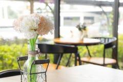 在桌上的白色人造花在咖啡馆 图库摄影