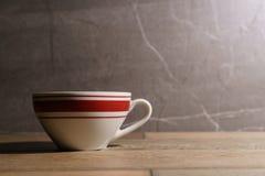 在桌上的白色和红色咖啡杯 图库摄影