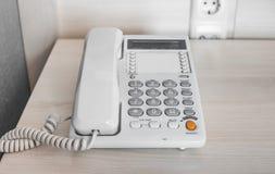 在桌上的白色电话在旅馆客房 免版税库存照片