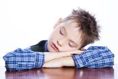 在桌上的睡觉的男孩 免版税库存照片