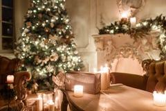 在桌上的礼物 由烛光的圣诞节晚上 与一个白色壁炉,装饰的树的经典公寓 图库摄影