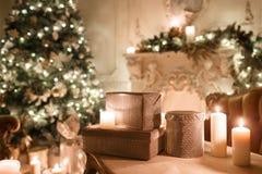 在桌上的礼物 由烛光的圣诞节晚上 与一个白色壁炉,装饰的树的经典公寓 库存图片