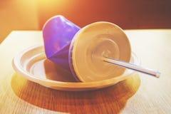在桌上的空和被弄皱的纸一次性半公升玻璃在午餐以后的一个咖啡馆 免版税库存图片